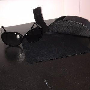 Women's fully black Prada sunglasses.